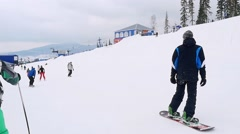 Snowboarder at ski resort after major snowstorm moves to the ski lifts Stock Footage