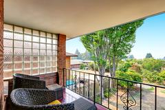 Balcony with wrought iron railing and black wicker chairs. Backyard view. Nor Stock Photos