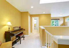Bright hallway interior with yellow walls and piano . Northwest, USA Stock Photos