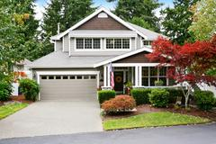 Nice curb appeal of grey house with garage and driveway. Column porch with Am Stock Photos