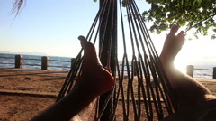 Feet wiggling in the sun in a hammock by the sea Stock Footage