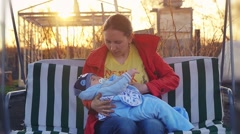 Woman breastfeeds her little child outdoor on swing in slowmotionduring sunset Stock Footage