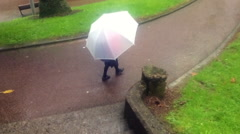 School girl with umbrella in a rainy day Stock Footage