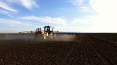 Tractor sprinkles the field with chemicals in sunny spring day. Stock Footage