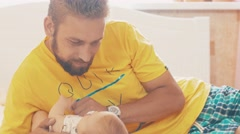 Bearded father lie with little baby. Parent. Family. Communication. Fatherhood Stock Footage