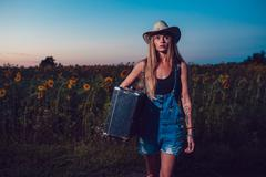 Young woman with retro suitcase traveling in countryside, summer nature outdoor Stock Photos
