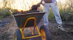 Worker throwing ground in a handcart during sunset in slowmotion with lens flare Stock Footage