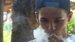 Young man trying to blow O's, slow motion Stock Footage