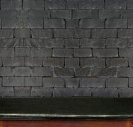 Empty black marble table and white black brick wall in background. product di Stock Photos