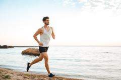 Handsome man athlete running at the beach Stock Photos