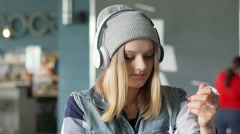 Hipster girl trying to untangle earphones and connecting them to smartphone Stock Footage