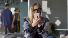 Pretty girl using smartphone as a mirror and painting her lips Stock Footage