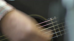 Musician plays 6-string acoustic guitar, obscured by microphone stand. Stock Footage