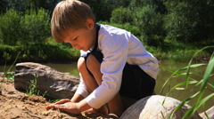 Small boy sits in a log on the bank of a pond Stock Footage