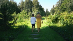 Girl and boy go on a forest path holding hands. back view. HD cinemagraph Stock Footage