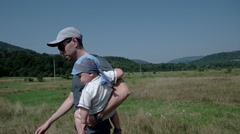 Little Child Being Carried by His Father Outside in the Field Stock Footage