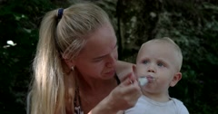 Mother Feeding Her Baby Boy With a Spoon. Mother Giving Food to Her Adorable Stock Footage
