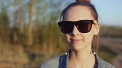 Young, stylish, informal girl looks around, takes off sunglasses. Stock Footage