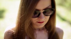 Beautiful young fashion girl in sunglasses with red lips corrects long hair. Stock Footage