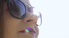 Beautiful girl in sunglasses with red lips enjoying the sunlight on nature. Stock Footage