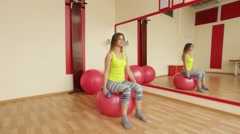 Young girls trainers biceps using dumbbells while sitting on a fitball. Stock Footage