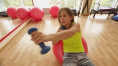 Young and beautiful girl pumps obliques lying on fitball in fitness club. Stock Footage
