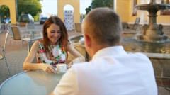 Loving couple sitting at a table in an open-air restaurant. Stock Footage