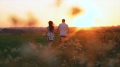 Young pair of runs in the sunset, the man picks up the girl and turns around Stock Footage