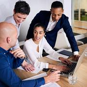 Group of four executives working together to brainstorm promotional ideas Stock Photos