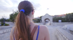 Woman walk towards Nin city gate over shoulder view 4K Stock Footage