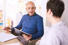 Young man holding tablet during a meeting with business woman Stock Photos