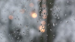 Winter snow string lights through a glass window with ice Stock Footage