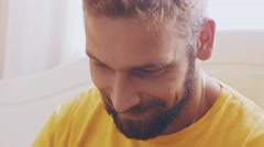 Portrait of bearded adult man in yellow shirt play in game on tablet. Smile Stock Footage