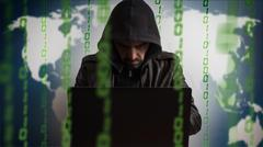 Hacker in a hood with laptop. Online network danger Stock Photos