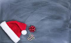 Erased black chalkboard with Santa cap and candy canes plus gift bow Stock Photos