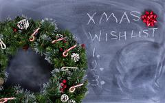 Erased black chalkboard with holiday wreath plus text writing Stock Photos