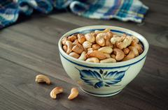 Roasted cashews on natural wooden table background Stock Photos