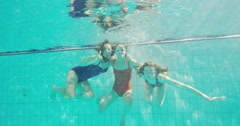 Young female friends in a swimming pool having fun together underwater Stock Footage