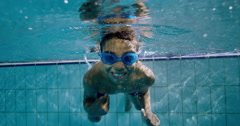 Happy cute little boy underwater is waving and smiling at the camera Stock Footage