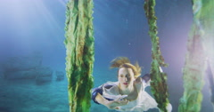 Beautiful mysterious woman with flowing blonde hair in a vibrant underwater Stock Footage