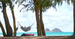 Young man reading a book on hammock exotic beach Stock Footage