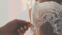 Buttoning the wedding dress Stock Footage