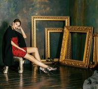 Beauty rich brunette woman in luxury interior near empty frames Stock Photos