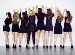 Many diverse women in line, wearing fancy little black dresses, party makeup Stock Photos