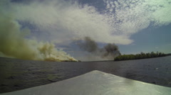 Boat approaches fires on opposite shorelines of lake Stock Footage