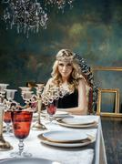 Young blond woman wearing crown in fairy luxury interior with empty antique Stock Photos