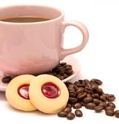 Cup of freshly brewed coffee and some strawberry cookies Stock Photos