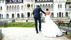 Bride and groom running in the rain in front of a beautiful castle Stock Footage