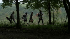 Young family walking through the forest, people refugees, pan right, tilt up. Stock Footage