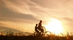 Father and son riding one bike together on sunny summer evening Stock Footage